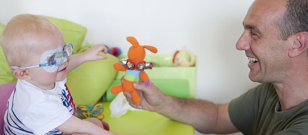 Un kinésithérapeute joue avec un enfant au centre d'action médico-sociale précoce