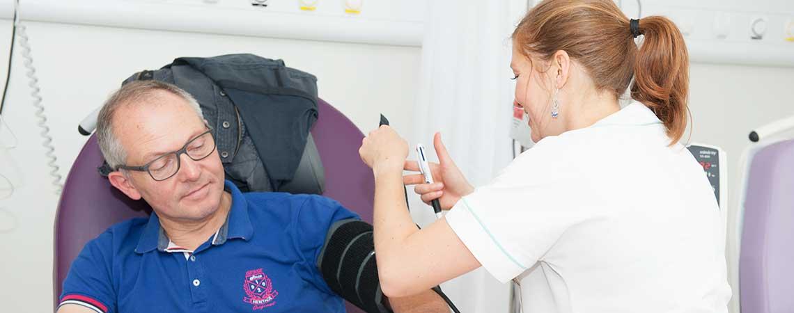 Infirmière prenant la tension d'un patient à l'hôpital de jour commun de rhumatologie, neurologie et douleur.