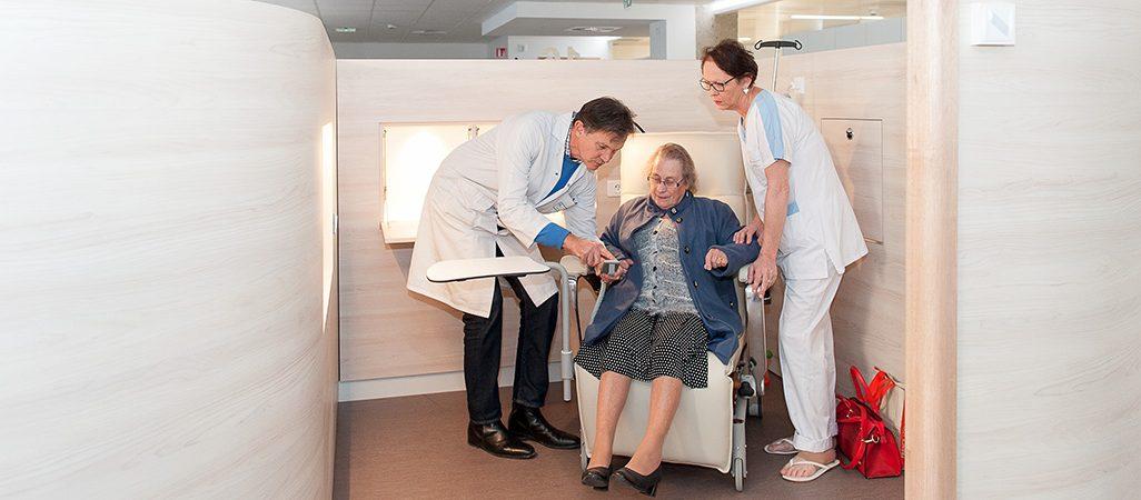 Le Pr Michel est avec une patiente âgée et une soignante dans l'un des cocons de l'hôpital de jour uro-digestif et oncologie.