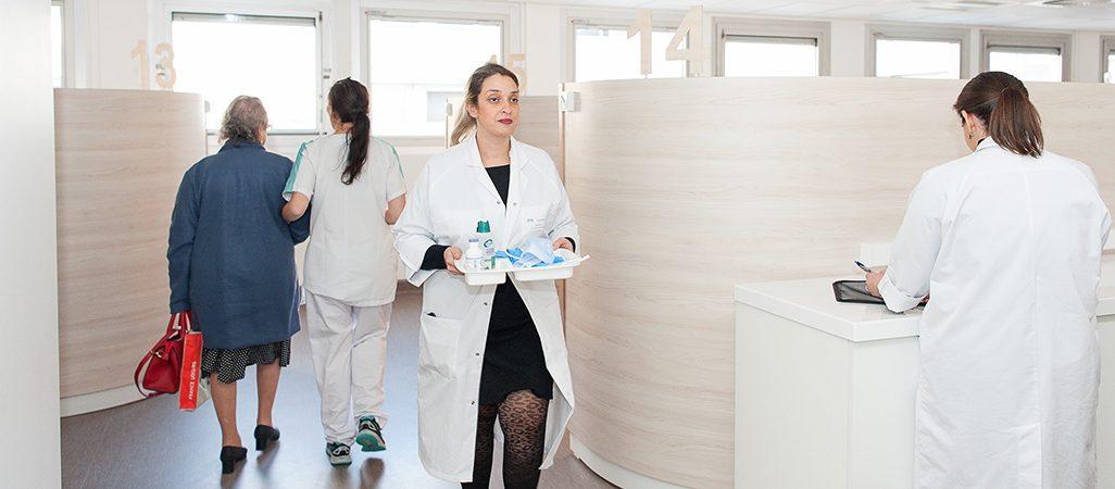 Une patiente et des soignantes se déplacent dans l'hôpital de jour uro-digestif et oncologie.