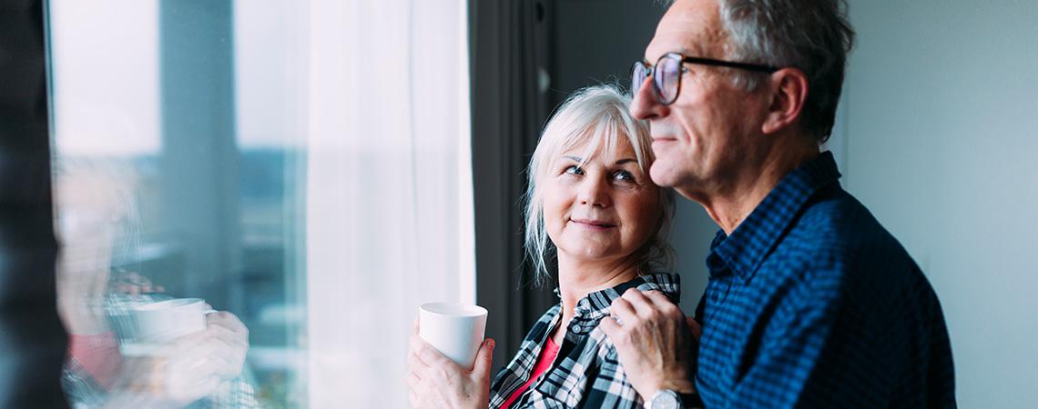 Un couple de personnes d'une soixantaine d'années se trouvent devant une fenêtre