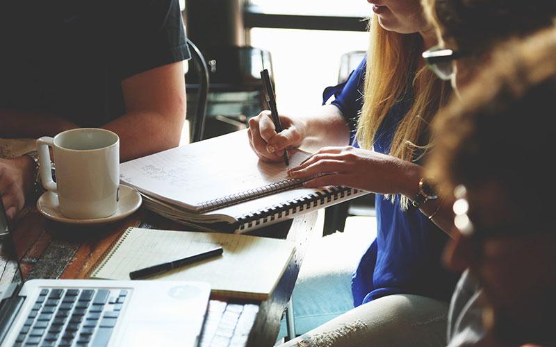 Des personnes sont réunies en réunion de travail autour d'un café.