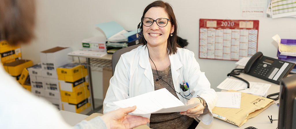 une secrétaire en chirurgie-gynécologie-cancer_ donne un document à une patiente