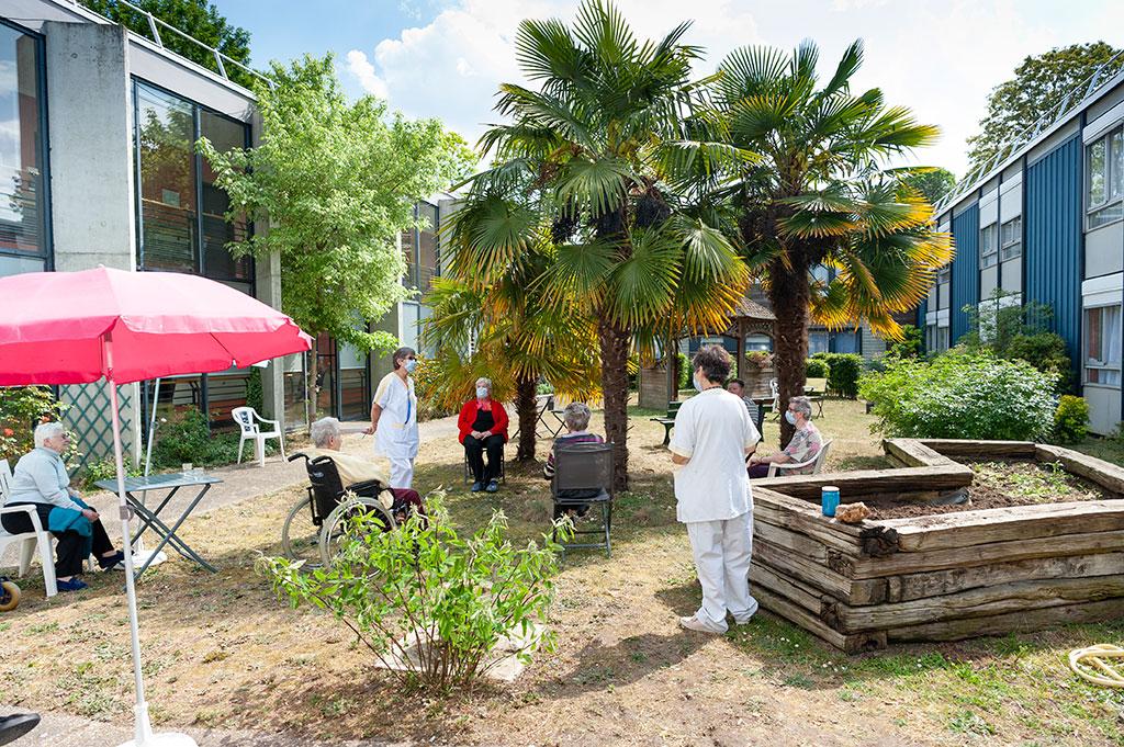 Des soignants et des résidents se trouvent dans le jardin de l'EHPAD Saint-Julien.