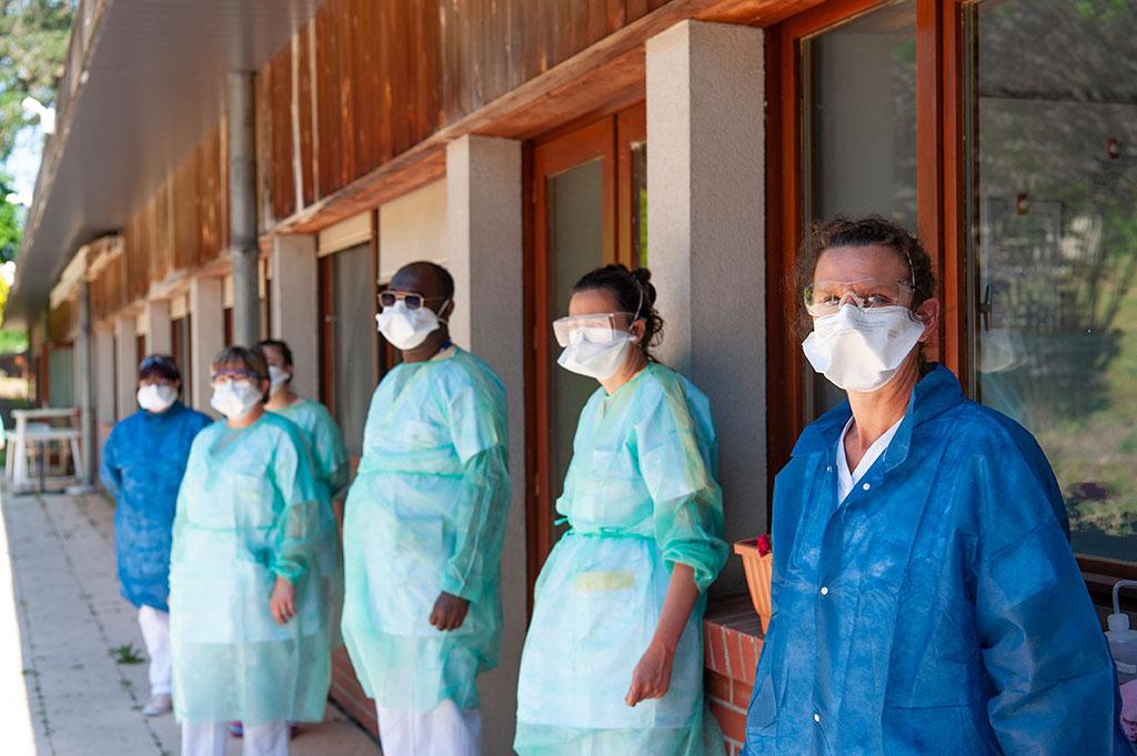Des soignants en tenues de protection Covid-19 sont alignés face à un bâtiment à l'hôpital de Oissel.