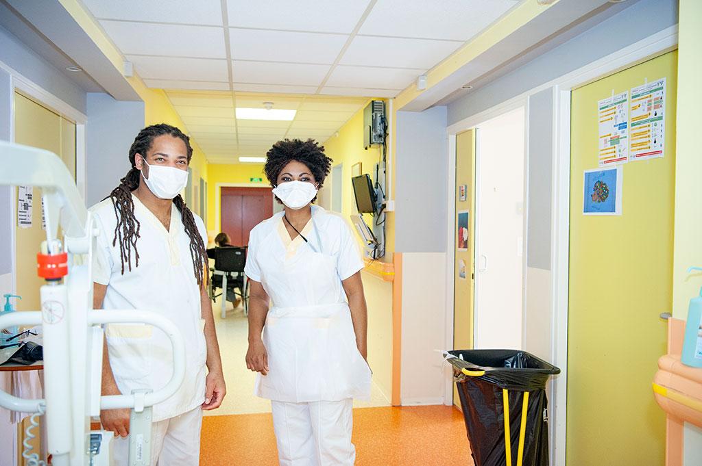 Deux soignants masqués pose dans un couloir de l'USLD Arcadie à l'hôpital de Boucicaut.