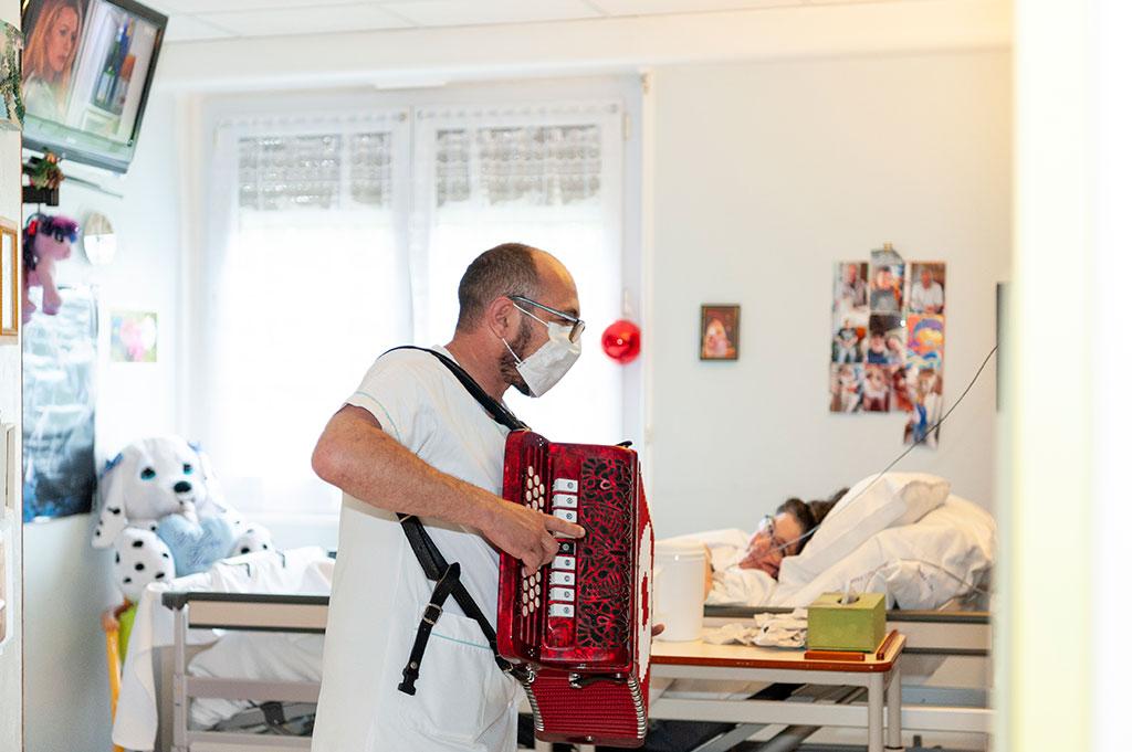 Un animateur joue de l'accordéon dans la chambre d'une résidente de l'hôpital de Boucicaut.