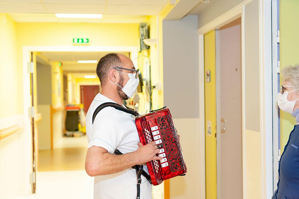 Un animateur joue de l'accordéon dans les couloirs de l'hôpital de Boucicaut.