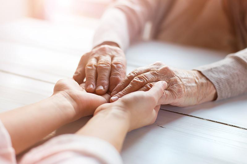Une personne âgées et une personne plus jeune se teinne les mains sans que l'on puisse voir leurs visages