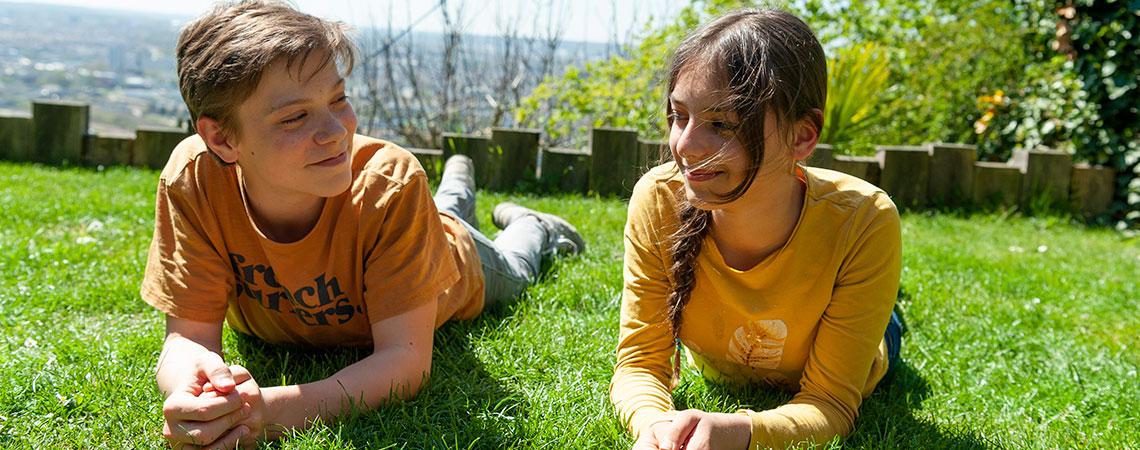 deux adolescents garons et filles allongés dans l'herbe, vaccination anti-HPV, juin vert